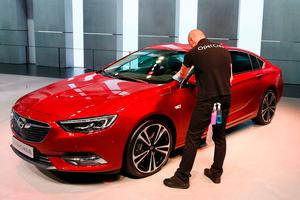 A worker cleans a new Opel Insignia car during the 87th International Motor Show at Palexpo in Geneva, Switzerland, March 7, 2017. REUTERS/Arnd Wiegmann