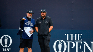 Shane Lowry of Ireland with his caddy on the 1st tee box during Day Four