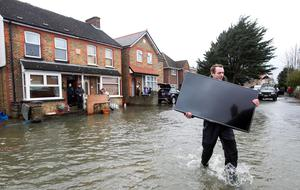A member of the army carries a television to higher ground in Egham, Surrey. Steve Parsons/PA Wire
