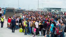 Final leg of Hellish journey: Thousands of refugees wait to board buses from the Austrian-Hungarian border to a train station in the Austrian village of Nickelsdorf