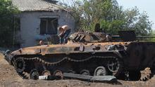 People loosen parts from a burned-out Ukrainian armored personnel carrier in the village of Hrabske, eastern Ukraine, Sunday, Aug. 31, 2014.