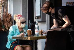 A server brings out sweetener to patron Francesca Macartney Beale at Douro restaurant in Connecticut at outdoor seating at socially-distanced tables. Employees must wear masks.  (Photo by John Moore/Getty Images)