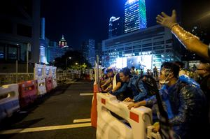 Protesters push a traffic barrier to block the main street to the financial Central in Hong Kong September 28, 2014