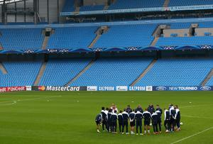 Manchester City manager Manuel Pellegrini talks to his players before training at the Etihad Stadium