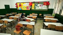 A worker cleans a classroom desk of a school closed as a precaution against the spread of the coronavirus in Sidon, Lebanon. Photo: REUTERS/Ali Hashisho