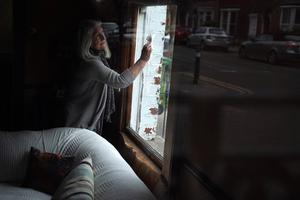 A woman cleans the window of her house, with the empty street reflected in the opposite window as the spread of coronavirus disease (COVID-19) continues, in Dublin. Photo: REUTERS/Clodagh Kilcoyne