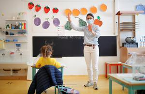 A teacher, wearing a protective face mask, teaches to schoolchildren in a classroom at a private school during its reopening in Saint-Sebastien-sur-Loire near Nantes as a small part of French children head back to their schools with new rules and social distancing during the outbreak of the coronavirus disease (COVID-19) in France, May 12, 2020.  REUTERS/Stephane Mahe