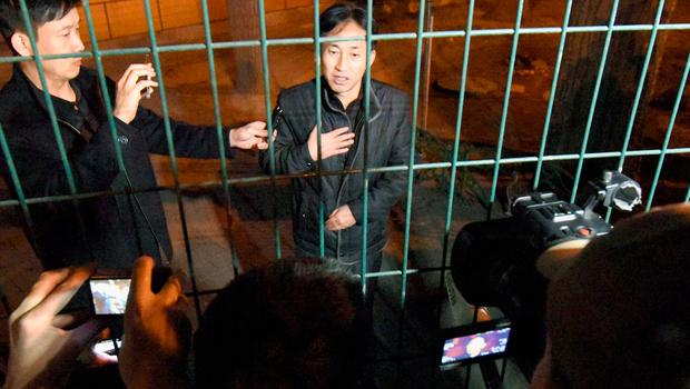 North Korean Ri Jong Chol, right, speaks to reporters from behind a fence at the North Korean Embassy in Beijing early Saturday, March 4, 2017.  (Minoru Iwasaki/Kyodo News via AP)
