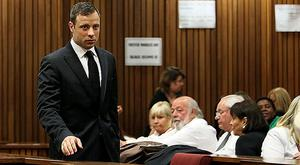 Oscar Pistorius walks past members of Reeva Steenkamp's family in the Pretoria courtroom where he was found guilty of culpable homicide