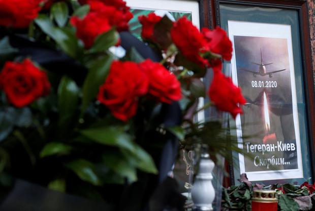 Flowers and a memorial poster are placed outside the Iranian Embassy to commemorate the victims of the Ukraine International Airlines flight PS752 plane crash, in Kiev, Ukraine January 8, 2020. The words on the poster read: