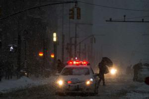A New York City Police car drives down Broadway in New York's financial district near Wall Street during a snow storm
