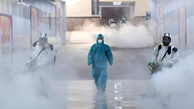 Cleaning up: Volunteers in protective suits disinfect a railway station in Changsha, Hunan province. Photo: Reuters