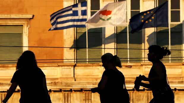 Tourists are silhouetted against the parliament where the flags of Greece, Cyprus and the EU are fluttering in Athens, Greece June 24, 2015. Prime Minister Alexis Tsipras flew to Brussels to meet Greece's international creditors on Wednesday to try to bridge gaps on key elements of the proposals made by his left-wing government to shore up state finances in return for vital loans.  REUTERS/Yannis Behrakis