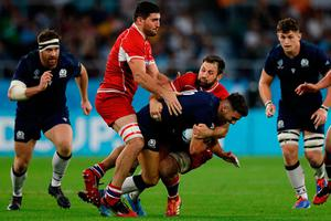 Scotland's fly-half Adam Hastings (C) is tackled. Photo: ADRIAN DENNIS/AFP via Getty Images