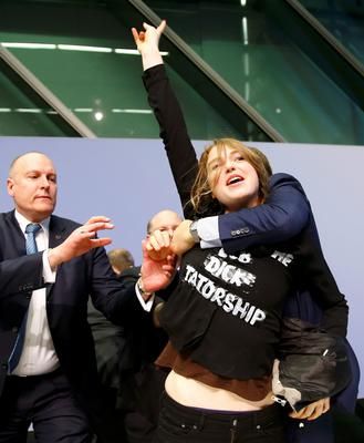 Security officers detain a protester who jumped on the table in front of the European Central Bank President Mario Draghi during a news conference in Frankfurt