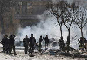 Civilians and civil defence members inspect the damage as smoke rises at a site hit by what activists said was a barrel bomb dropped by forces loyal to Syria's President Bashar al-Assad in the Qadi Askar neighbourhood of Aleppo. Reuters/Abdalrhman Ismail