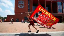 Liverpool fan Dillon Parry waves a flag outside Anfield yesterday after Liverpool ended their 30-year wait for a 19th top-flight title on Thursday night