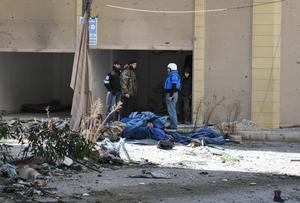 An United Nations World Food Programme (WFP) worker (R) talks with rebel fighters on February 8, 2014 on the second day of a humanitarian mission in a besieged district of the central city of Homs.