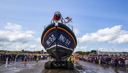 Wave of support: The lifeboat is welcomed into port. Photo: Patrick Browne