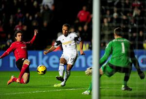 Cardiff player Fabio (l) and keeper David Marshall look on as Wayne Routledge scores the opening goal