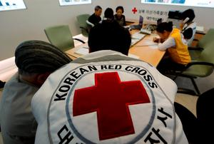 South Koreans who were separated from their families during the Korean War, talk with Red Cross members as they check application forms to reunite with their family members living in North Korea, at the Korea Red Cross headquarters in Seoul, South Korea (AP Photo/Lee Jin-man)