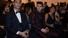Cristiano Ronaldo sits next to Lionel Messi and his wife