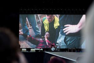 Foo Fighters band member Dave Grohl is seen on a big screen talking on a microphone after falling from the stage during the band's concert at Nya Ullevi in Gothenburg, Sweden