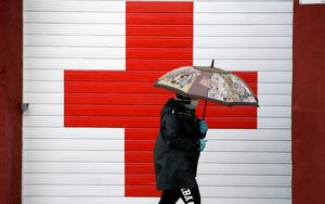 A woman wearing a mask and gloves walks past Red Cross offices during a partial lockdown as part of a 15-day state of emergency to combat the coronavirus outbreak in the Asturian town of Oviedo, Spain. Photo: REUTERS/Eloy Alonso