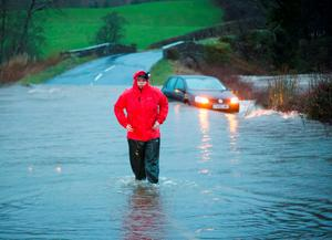A person wades through flood water in Straiton, Scotland, as Storm Frank begins to batter the UK on its way towards flood-hit areas. Photo: PA