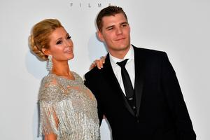 US socialite Paris Hilton (L) and her partner US model Chris Zylka pose as they arrive for the amfAR's 24th Cinema Against AIDS Gala on May 25, 2017 at the Hotel du Cap-Eden-Roc in Cap d'Antibes, France. / AFP PHOTO / ALBERTO PIZZOLI