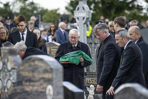 The slain detective's father, Marty, holds a Tricolour at the graveside. Picture: Mark Condren