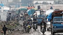 Moving out: Men on motorbikes pass trucks carrying the belongings of displaced Syrians in Idlib. Photo: Khalil Ashawi/Reuters