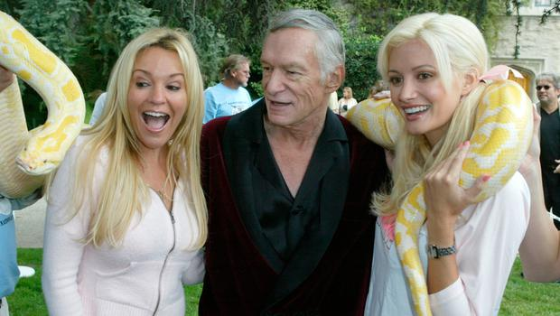 Bridget Marquardt, Hugh Hefner and Holly Madison pose with a snake as they arrive at the 10th Annual Safari Brunch on October 16, 2004 at the Playboy Mansion in Beverly Hills, California. (Photo by Frazer Harrison/Getty Images)