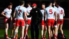 Tyrone manager Mickey Harte talks to his players before the match