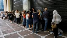Queues outside a branch of the Piraeus Bank in Athens yesterday after Greek Prime Minister Alexis Tsipras called a referendum on austerity demands