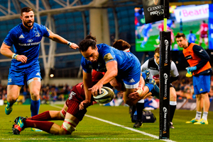 Leinster's James Lowe goes over to score his side's third try despite the efforts of Munster's Jean Kleyn. Photo: Harry Murphy/Sportsfile