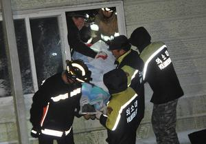 ATTENTION EDITORS - VISUAL COVERAGE OF SCENES OF INJURY OR DEATH  Rescue workers carry the body of a university student who was trapped by debris from a collapsed resort in Gyeongju, south of Seoul in this February 17, 2014 photo courtesy of News1.  At least six students were killed and some 50 others remained trapped in debris after a resort building collapsed late Monday, according to police officials. REUTERS/Noh Hwa-jung/News1  (SOUTH KOREA - Tags: DISASTER EDUCATION) ATTENTION EDITORS -  NO SALES. NO ARCHIVES. FOR EDITORIAL USE ONLY. NOT FOR SALE FOR MARKETING OR ADVERTISING CAMPAIGNS. THIS IMAGE HAS BEEN SUPPLIED BY A THIRD PARTY. IT IS DISTRIBUTED, EXACTLY AS RECEIVED BY REUTERS, AS A SERVICE TO CLIENTS. SOUTH KOREA OUT. NO COMMERCIAL OR EDITORIAL SALES IN SOUTH KOREA. TEMPLATE OUT