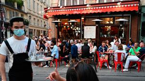 Poeple eat and take drinks at the terrace of the cafe-restaurant 'Bar du Marche' in Paris as cafes and restaurants reopen in France. (Photo by BERTRAND GUAY/AFP via Getty Images)