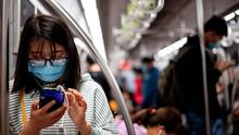 A passenger wearing a facemask uses her mobile phones at the subway in Beijing. (Photo by Noel CELIS / AFP) (Photo by NOEL CELIS/AFP via Getty Images)