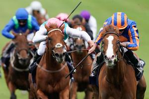 Ryan Moore riding Love (R, blue/orange) to victory in the Qipco 1000 Guineas Stakes at Newmarket Racecourse. Photo: Alan Crowhurst/Getty Images