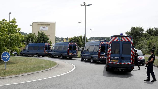 Riot police officers block the area where an attack took place, Friday, June 26, 2015 in Saint-Quentin-Fallavier, southeast of Lyon, France.  A man with suspected ties to French Islamic radicals rammed a car Friday into an American gas factory in southeastern France, triggering an explosion that injured two people, officials said. The severed head of a local businessman was left hanging at the factory's entrance, along with banners with Arabic inscriptions, they said. (AP Photo/Laurent Cipriani)