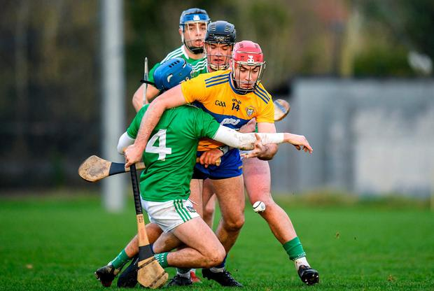 Niall Deasy of Clare is tackled by Aaron Costello, Paddy O'Loughlin and David Reidy. Photo: Harry Murphy/Sportsfile