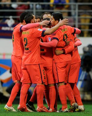 Barcelona players celebrate after Argentinian forward Lionel Messi scored on a penalty kick during the Spanish league football match SD Eibar vs FC Barcelona at the Ipurua stadium in Eibar on March 14, 2015.   AFP PHOTO/ ANDER GILLENEAANDER GILLENEA/AFP/Getty Images