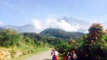 Tourists walk away from Mount Kinabalu hours after a magnitude 5.9 earthquake shook the area in Kundasang, Sabah, Malaysia