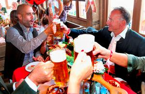 Bayern's coach Pep Guardiola, left, and the club's president Karl-Heinz Rummeingge, right, lift a glass of beer as the players of FC Bayern Munich visit the Oktoberfest beer festival 2015 at Theresienwiese in Munich, southern Germany, Wednesday, Sept. 30, 2015. (Alexander Hassenstein/pool via AP)