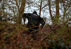 A police officer searches the undergrowth in  Dawsholm Park in Glasgow  after the handbag which police believe belongs to missing student Karen Buckley was found early this afternoon. Photo credit: Andrew Milligan/PA Wire