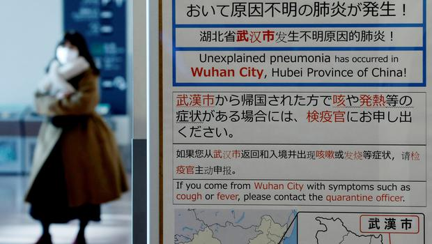 FILE PHOTO: A woman wearing a mask walks past a quarantine notice about the outbreak of coronavirus in Wuhan, China at an arrival hall of Haneda airport in Tokyo, Japan, January 20, 2020. REUTERS/Kim Kyung-Hoon/File Photo