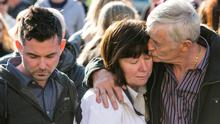Grief etched across their faces, John Buckley leans across and tenderly kisses the forehead of his wife Marian as they and their son Kieran (left) are surrounded by 800 people who turned out to show their sympathy as the family mourn their daughter Karen