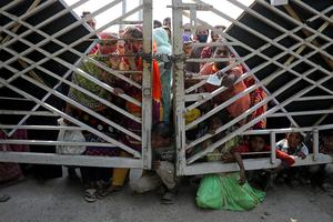 Life on the margins: People wait outside of a gate to receive relief supplies provided by local police authorities amid the Covid-19 outbreak in Dhaka, Bangladesh. Photo: REUTERS