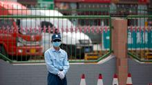 A security officer stands guard outside the Xinfadi wholesale food market district in Beijing. Beijing closed the city's largest wholesale food market Saturday after the discovery of seven cases of coronavirus. AP Photo/Mark Schiefelbein